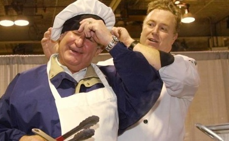 Former Premier Ralph Klein, reluctantly doning a chef's hat.