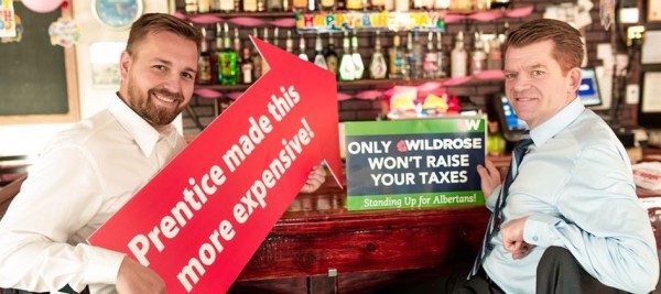 Wildrose leader Brian Jean (right) and Strathmore-Brooks candidate Derek Fildebrandt use a comically large arrow to point out tax increases to alcohol included in the PC Party's recent provincial budget.