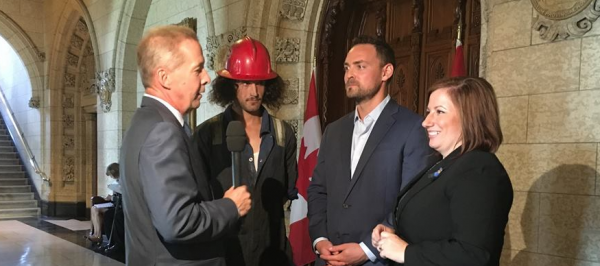 Neil Bernard Hancock (second from left), Mark Scholz (second from right) and Shannon Stubbs (left) being interviewed on Parliament Hill.