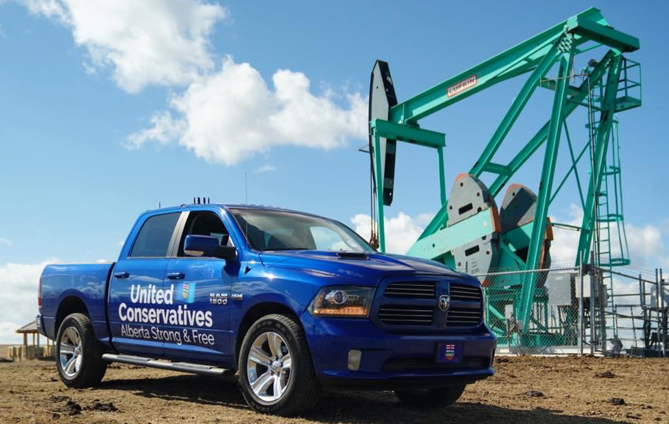 The United Conservative Party's infamous blue campaign truck parked near a pumpjack (source: Facebook) (source: Facebook)