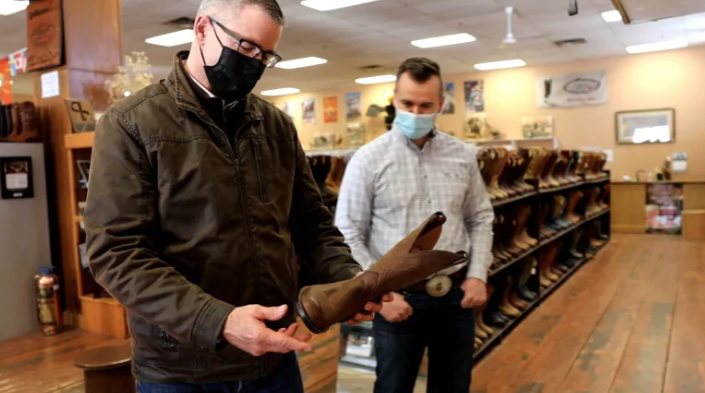 Finance Minister Travis Toews buys a pair of cowboy boots to mark this year's budget.